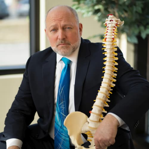 Doctor holding model of a spine